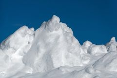 Large Snow Pile Against Dark Blue Sky royalty free stock image