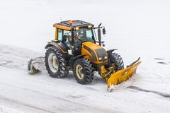 Large snow plowing tractor machine at work on the road during a snow storm in winter. Stock Image