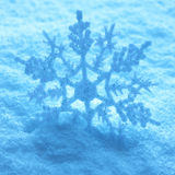 Large snowflake on snow. Macro view of large blue toned snowflake on icy or frozen background Royalty Free Stock Photography