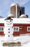 Large snowman in front of barn with silos Stock Image