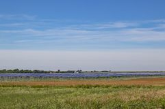 Large solar farm out on the plains with a low horizon and farm in distance under pretty blue sky royalty free stock image