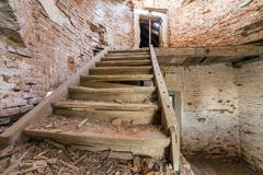 Large spacious forsaken empty basement room of ancient building or palace with cracked plastered brick walls, dirty floor and stock images