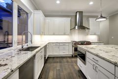 Large, spacious kitchen design with white kitchen cabinets royalty free stock image