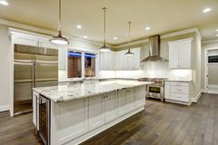 Large, spacious kitchen design with white kitchen cabinets. White kitchen island with lots of storage, white Granite countertops, subway tiles and stainless Royalty Free Stock Image