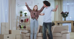 In a large spacious living room charismatic couple carrying a big sofa in the living room enjoying the time in a new stock footage