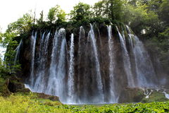 Large sprinkle waterfall. With clear fresh water in Plitvice lakes national park surrounded by green grass and old trees Stock Image