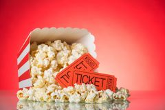Large square box with crumbled popcorn and movie tickets on brig. A large square box with crumbled popcorn and movie tickets on a bright red background Stock Photography