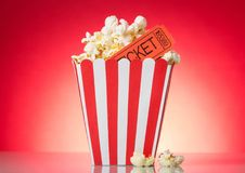 Large square box with popcorn and movie tickets on bright red . A large square box with popcorn and movie tickets on a bright red background Royalty Free Stock Images