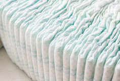 A large stack of baby diapers, close-ups, diaper packaging stock photography