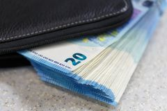 Large stack of money worth 20 euros are stick out of the purse stock photo