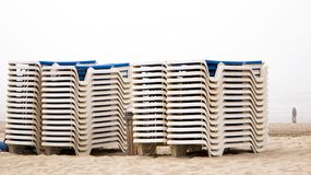 A stack of deckchairs provide interesting lines as they await beach goers Stock Photo