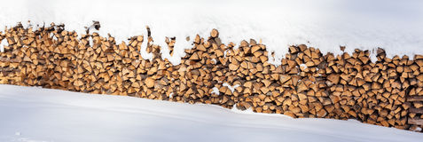 Large Stack of Wooden Logs Piled up Outside and Covered in Snow Stock Image