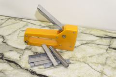 Large stapler and staples for construction work on white.  stock photo