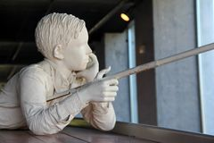 Large statue of young boy fishing off side of canal boat during life along the Eerie Canal, Syracuse, New York, 2017. Large statue of young child fishing off the Royalty Free Stock Photography