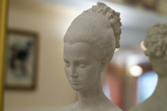 Large statuette on the fireplace in the banquet hall. Head of a girl with curly hair. royalty free stock image