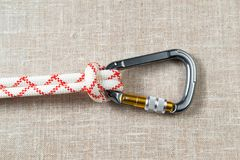 Large steel carabiner for mountaineering with red-white rope. On textured fabric background Stock Image