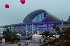 Large steel and glass building. Oval roof of the building, blue lights, stone stairs. Red gel balls in the air. Guangzhou Exhibition Center royalty free stock photos