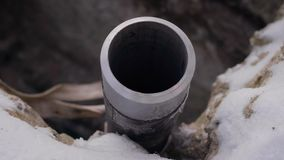 Large steel pipe of industrial equipment is fixed in frozen ground outdoors, camera is moving around stock footage