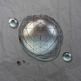 Large steel sphere. With a glossy color reflections in the iron lattice and small glass spheres on a dark background of crumpled paper with the addition of Stock Photo