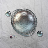 Large steel sphere. With a glossy color reflections in the iron lattice and small glass spheres on a light background of crumpled paper with shadows added Royalty Free Stock Image