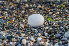 A large stone amid pebbles. Large round and bright stone on a background of multicolored sea pebbles Royalty Free Stock Image