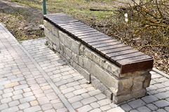 Large stone bench. Covered with boards royalty free stock photo