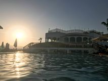 A large stone building near the water, a pool against the blue sky and a big sun, a sunset in the evening in a tropical seaside re. Sort royalty free stock photos