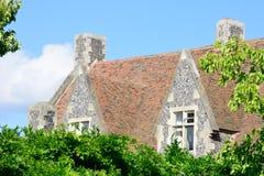 Large stone cottage behind green  trees. Large english stone cottage behind green  trees Stock Images