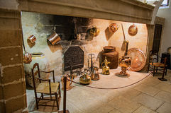 Large stone fireplace with decorative copper kitchenware and chairs in Lourmarin castle. royalty free stock photo