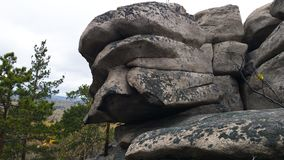 A large stone hanging on the edge of the rock in the shape of a person`s face. Walk along the Arakul Shihan in Russia. A large stone hanging on the edge of the stock photography