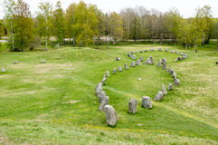 Large stone ship. Made of raised stones in Anundshog, Sweden. Also seen are burial mounds in the field Royalty Free Stock Photos