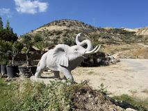 Large stone statue of an elephant with a raised trunk. One large stone statue of an elephant with a raised trunk Stock Photo
