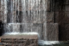 Large stone wall with water splashing from above. Large stone wall with different sizes and shapes of rock and waterfall splashing from above Royalty Free Stock Photos