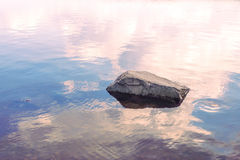 Large stone in the water against the evening sky Royalty Free Stock Images