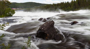 A large stone in a wild river Stock Image