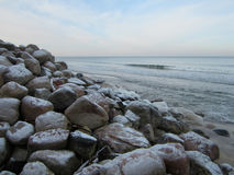 Large stones. Lay on the sand next to the sea waves Royalty Free Stock Images