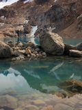 Large Stones Lying in a Turquoise Mountain Lake. Mountain Reflecting in the Water Surface. Stony Bank. royalty free stock image