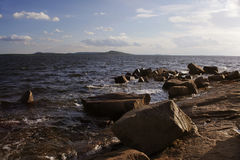 Large stones in the sea near the rocks, illuminated by the sun. In the background is the island Royalty Free Stock Images