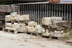 Large stones stacked in piles to be used to build house Stock Image