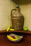 Large straw bottle and fruits Royalty Free Stock Photos