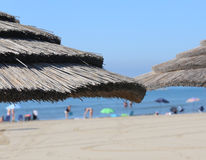 Large straw umbrella to shelter from the hot summer sun in the  Royalty Free Stock Photography