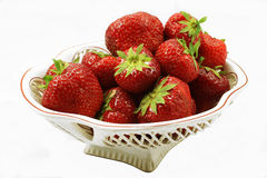 Large strawberry in a vase on a white background. The vase with a ripe strawberry, is photographed on a white background Stock Photos