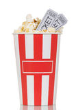 Large striped popcorn box and gray movie ticket isolated on white Stock Photos
