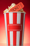 Large striped popcorn box with orange ticket to the movies on red background. Large striped popcorn box with orange a ticket to the movies on a bright red royalty free stock photo