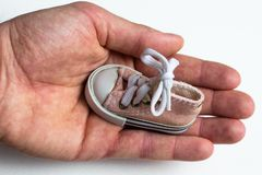 In a large and strong male hand is a small children`s shoes. On shoes tied with a bow bow. A hand with shoes on a white background that highlights them royalty free stock photos