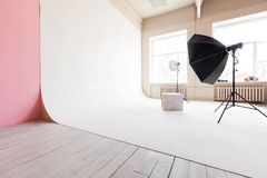 Large studio space white cyclorama and natural light from large windows. lighting equipment and flash Royalty Free Stock Image