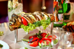Large stuffed fish with vegetables decorated herbs on the table. Stock Photography