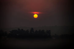 Large sun disk in dark sky at sunrise against defocused hills Royalty Free Stock Photography