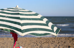 Large sun parasol on the shore of the ocean in the hot summer su Stock Images
