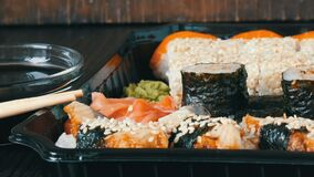 Large sushi set with a variety of sushi rolls as well as maki, nigiri, gunkan on a stylish black wooden background. A large sushi set with a variety of sushi stock video footage